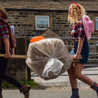 Competitors in fancy dress carrying a bale of straw during an annual running of the Oxenhope Straw Race